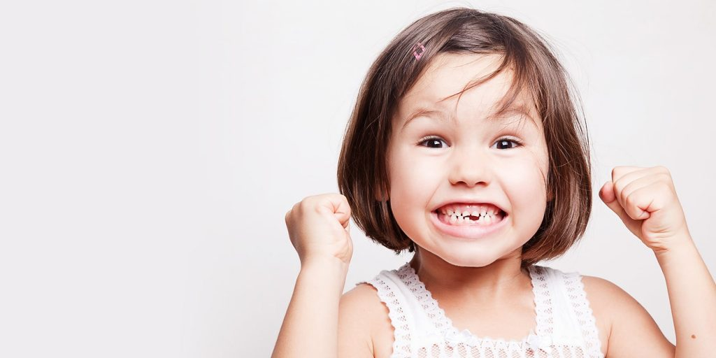 Little girl smiles a toothy grin